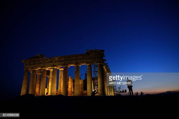 The ancient temple of Parthenon atop the Acropolis hill is iluminated in Athens on April 26 2016 / AFP / ARIS MESSINIS