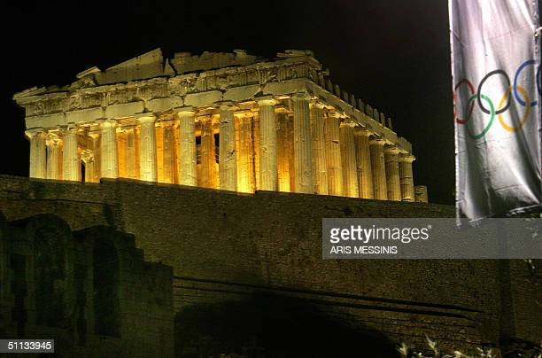 The ancient temple of the Parthenon is illuminated as part of a new lighting display on the Acropolis Hill in Athens 31 July 2004 as a flag with the...