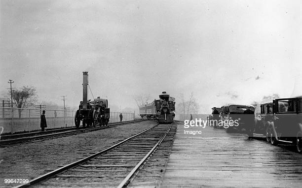 The ancient train carries Mr. Edison and President Hoover to Menlo Park in New Jersey. The picture shows the train during his ride through Dearborn,...