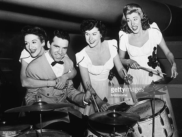 The Andrews Sisters clowning on stage with bandleader and drummer Buddy Rich LaVerne hugs Rich from behind while her sisters Maxene and Patty play...