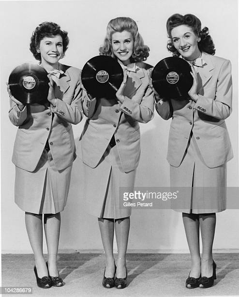The Andrews Sisters pose for a studio group portrait holding 10 inch records in 1941 in the United States