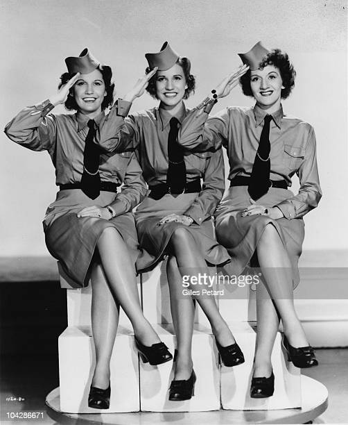 The Andrews Sisters pose for a studio group portrait saluting and wearing military uniforms in 1941 in the United States