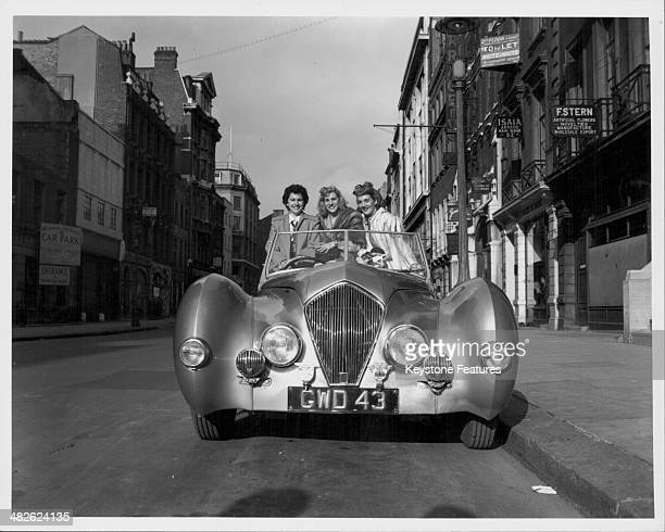 The Andrews Sisters posing for a photograph in a car Maxene Patty and LaVerne London 1948