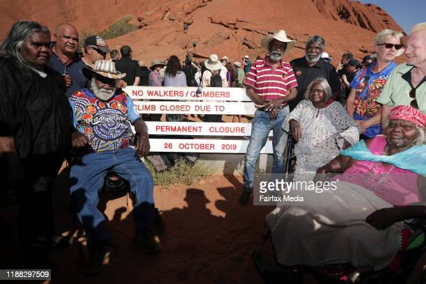 The Anganu, Uluru's traditional owners, stand next to the sign marking the closure of the walking track to the summit of Uluru in the Northern...