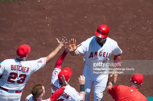 The Angels' Albert Pujols is greeted at the dugout steps after scoring on a Chris Iannetta sacrifice fly in the fourth inning scored during the...