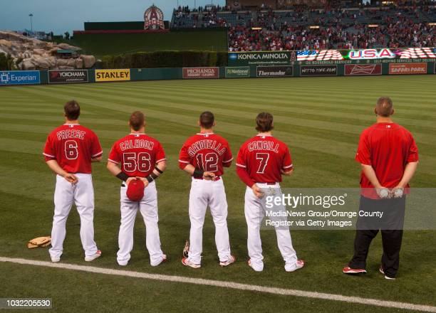The Angels' David Freese Kole Calhoun Johnny Giavotella and Collin Cowgill listen to the National Anthem next to strength and conditioning coach TJ...