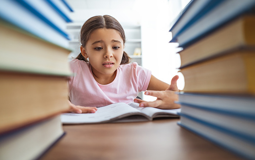 The angry schoolgirl sitting on the desk with books 1060220328