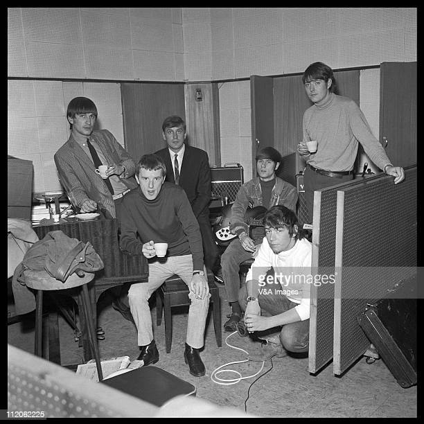 Dave Rowberry John Steel Mickie Most Hilton Valentine Eric Burdon Chas Chandler posed group portrait in recording studio with cups of tea 1965