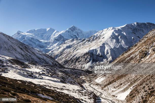 the annapurna iii and the gangapurna peaks in the himalays in nepal - didier marti stock photos and pictures