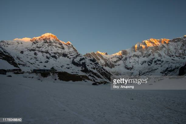the annapurna massif at sunrise view from annapurna base camp (4,130 m) in north-central nepal. - circondare foto e immagini stock