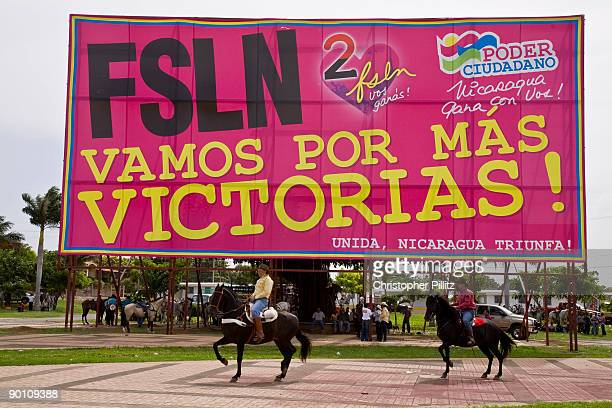 The annual horse parade to mark the patron saint of Managua Santo Domingo Seen here with large political posters extolling the 'victories' of the...