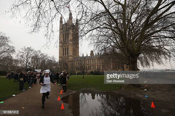 The annual Parliamentary Pancake Race takes place in front of the Houses of Parliament on Shrove Tuesday on February 12 2013 in London England Now in...