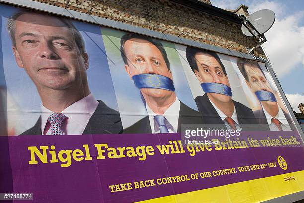 The anti-EU membership 'UK Independence Party's political billboard shows leader Nigel Farage and a gagged Prime Minister David Cameron, Labour party...