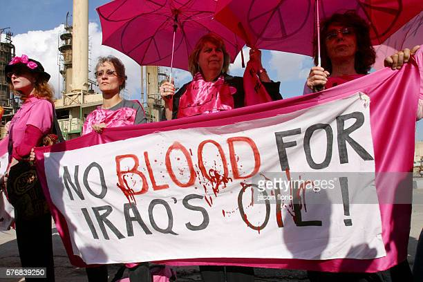 The antiwar activism group Ladies In Pink rallies in front a Baghdad oil refinery The group carries a sign which reads Giving blood for transfusions...