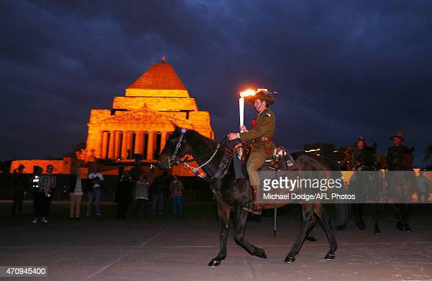 The Anzac torch is enroute by horse after being lit at The Shrine Of Remembrabce during the round four AFL match between the Richmond Tigers and the...