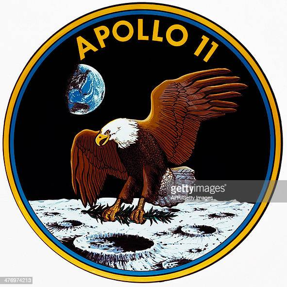 The Apollo 11 Mission insignia shows an eagle holding an olive branch in its claws as it lands on Moon's surface with the Earth rising in the...