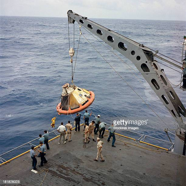 the apollo spacecraft command module is recovered aboard uss bennington. - space capsule stock photos and pictures