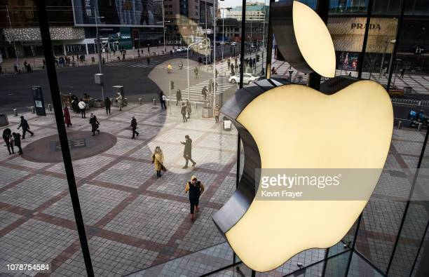 The Apple logo is seen on the window at an Apple Store on January 7 2019 in Beijing China Apple Inc lowered its revenue guidance last week blaming...