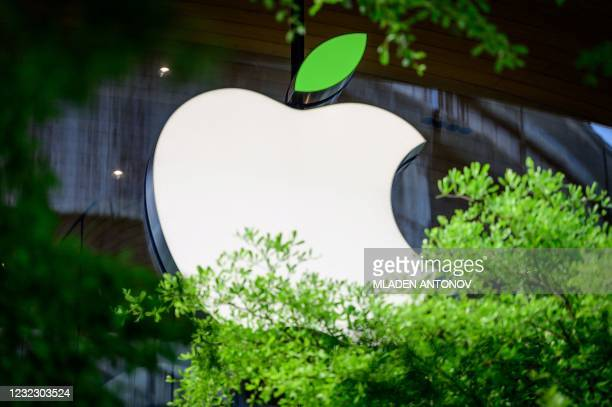The Apple logo sporting a green leaf to mark the upcoming Earth Day is seen on a window of the company's store in Bangkok on April 14, 2021.