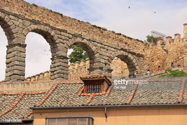 the aqueduct of segovia in plaza del azoguejo in segovia, spain and tiled rooftops of buildings - national landmark stock pictures, royalty-free photos & images