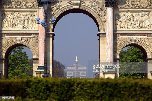 The Arc de Triomphe and the obelisk of the Place de la Concorde are show through the arc of the Louvre Carrousel in Paris on April 16 2010 AFP PHOTO...