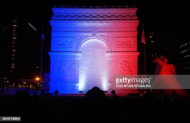 TOPSHOT The Arc de triomphe de l'Etoile snow statue is lit up during the Sapporo Snow Festival in Sapporo on Feburary 10 2017 The weeklong snow...