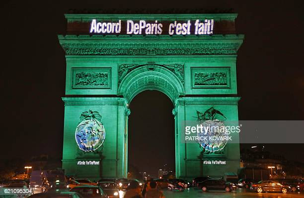 The Arc de Triomphe is illuminated with the lettering reading 'The Paris accord is done' in Paris on November 4 to celebrate the first day of the...