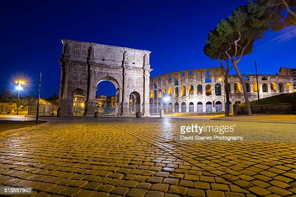The Arch of Constantine and Colosseum at sunrise in Rome, Italy