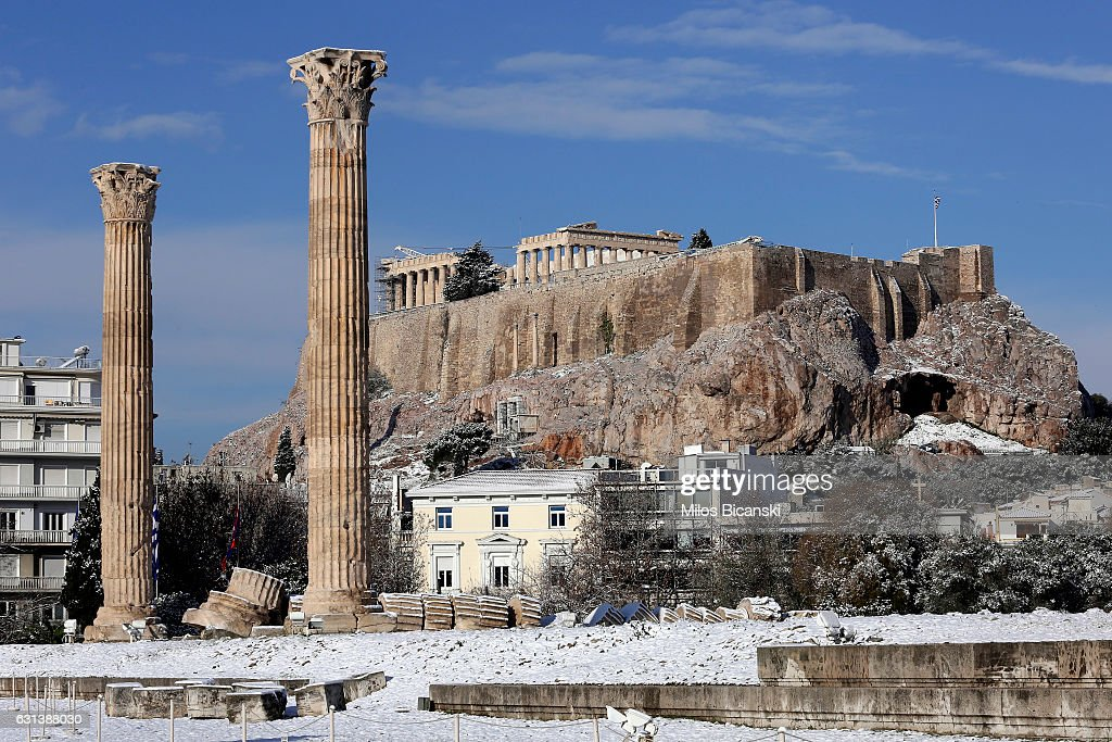 The Archaeological site of the ancient Temple of Zeus with the Acropolis Hill in the background which is covered in snow on January 10, 2017 in Athens, Greece. Schools in Athens remained closed on Tuesday and the rare snowfall caused traffic disruptions in the city centre.