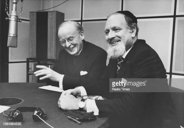 The Archbishop of Canterbury Donald Coggan and Immanuel Jakobovits Chief Rabbi of the UK sitting behind a microphone together at BBC Radio studios in...