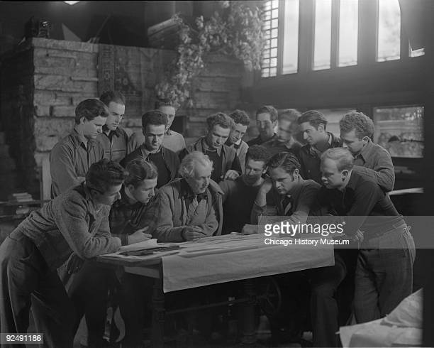 The architect Frank Lloyd Wright at a drafting table with several onlookers while at Taliesin East, in Spring Green, WI, December 1937.