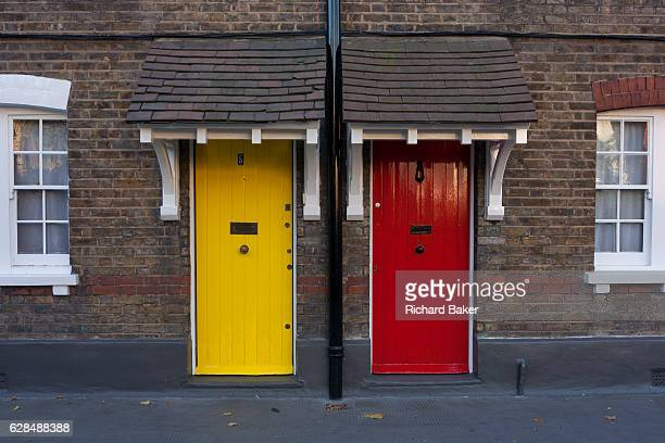 The architecture of neighbouring yellow and red painted front doors seen from the exteriors of Victorian cottages on 28th November 2016 at Winchester...