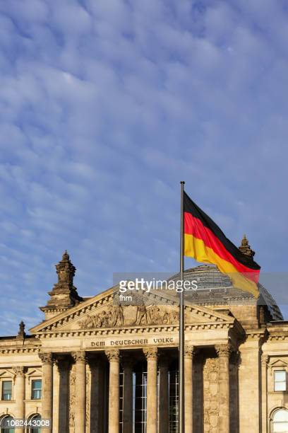 The architrave on the west portal of the Reichstag building in Berlin: 'Dem Deutschen Volke' with german flag