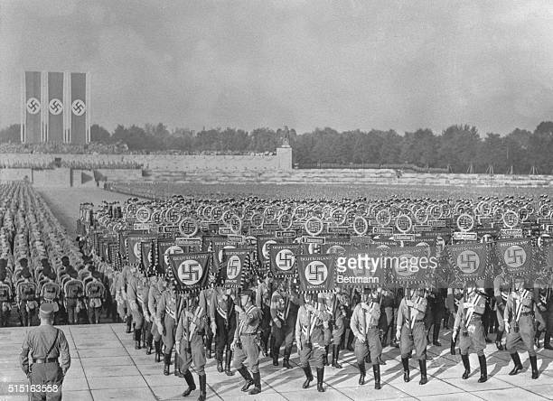 The arena of the stadium packed solidly with Storm Troopers and SS Men, carrying swastika banners, as 120,000 persons at the tenth Nazi party...