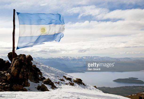 the argentine flag blows in the wind at the top of cerro catedral on a sunny day in the andes - argentinas flagga bildbanksfoton och bilder
