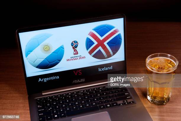 The Argentinian and Icelander flags seen together with the Russian 2018 World cup logo displayed on a laptop next to a glass of beer This game...