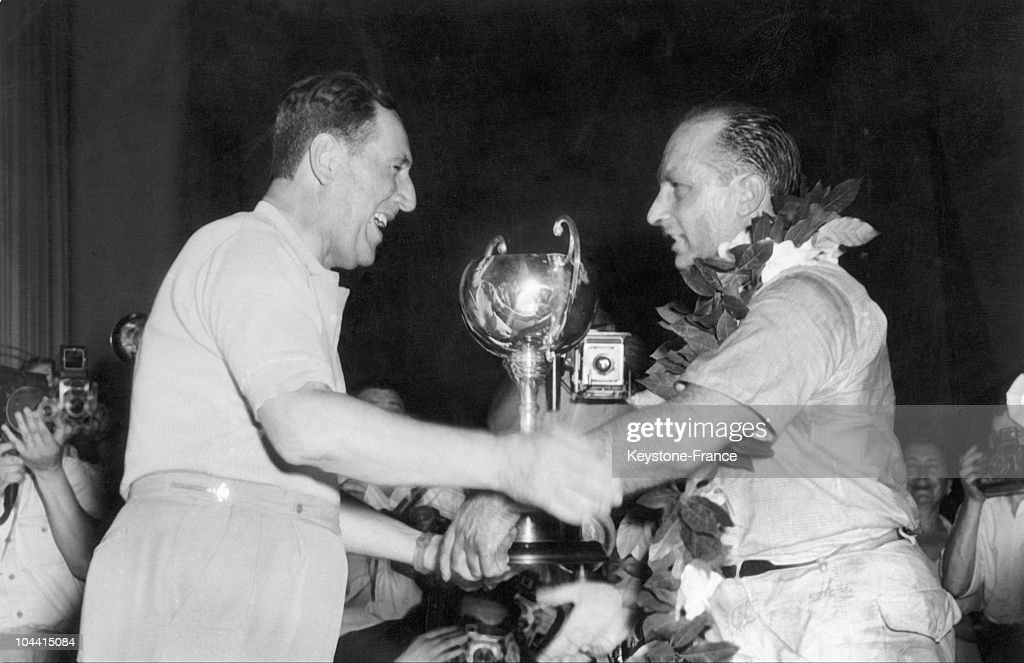 The Argentinian racecar driver Juan Manuel FANGIO, who had just won the Grand Prix of Argentine Buenos Aires, is congratulated by the President of the Argentine Republic, General Juan PERON, who is seen awarding him his trophy, in Buenos Aires.