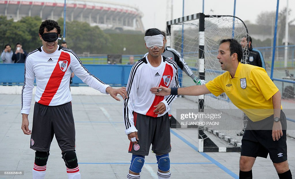 The Argentinian referee gives instructions to River Plate's footballers Oscar Mouzo (L) and Gustavo Maidana (C) during a blind football match of the Argentine FaDeC (Argentine Federation of Sports for the Blind) championship in Buenos Aires on May 21, 2106. Boca Juniors won 1-0. Five-a-side blind football is contested by teams made up of four visually impaired outfield players wearing blindfolds with a goalkeeper who may be fully sighted. The football they play with contains ball bearings to produce a noise when it moves. / AFP / ALEJANDRO