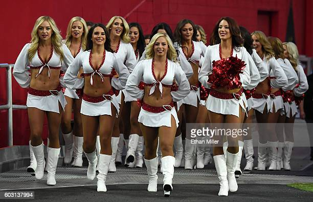 The Arizona Cardinals cheerleaders take the field before the team's NFL game against the New England Patriots at University of Phoenix Stadium on...
