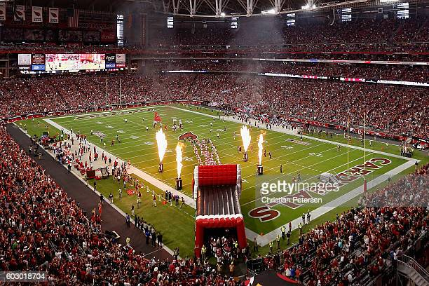 The Arizona Cardinals run onto the field for the NFL game against the New England Patriots at the University of Phoenix Stadium on September 11 2016...