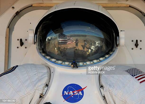 The Arizona desert is reflected in the bubble of a space suit helmet mounted to a 'suit port' on the outside of NASA's newest rover prototype Space...