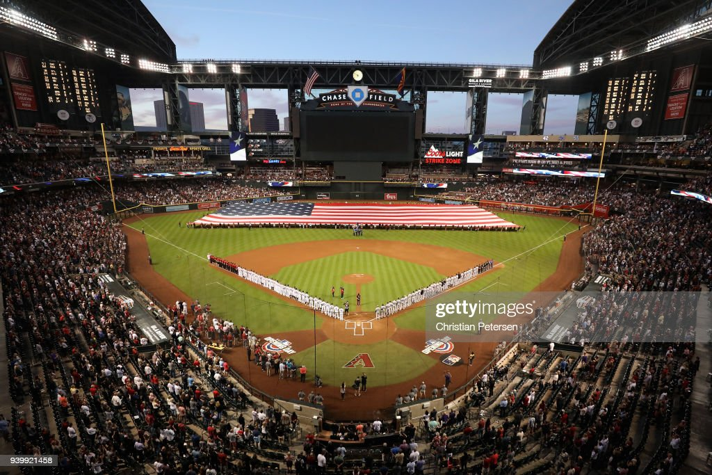 The Arizona Diamondbacks and the Colorado Rockies stand attended for the national anthem before the opening day MLB game at Chase Field on March 29, 2018 in Phoenix, Arizona.