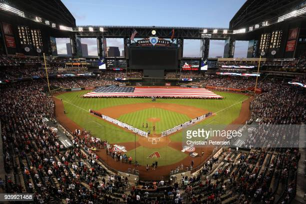 The Arizona Diamondbacks and the Colorado Rockies stand attended for the national anthem before the opening day MLB game at Chase Field on March 29...