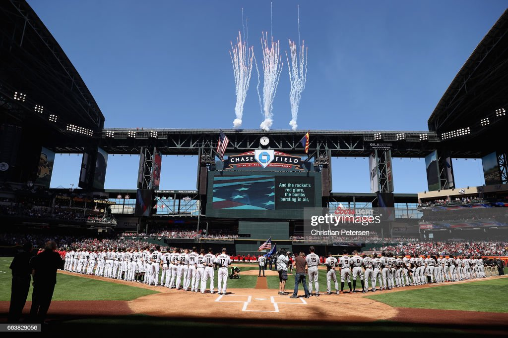 The Arizona Diamondbacks and the San Francisco Giants stand attended for the national anthem before the MLB opening day game at Chase Field on April 2, 2017 in Phoenix, Arizona.