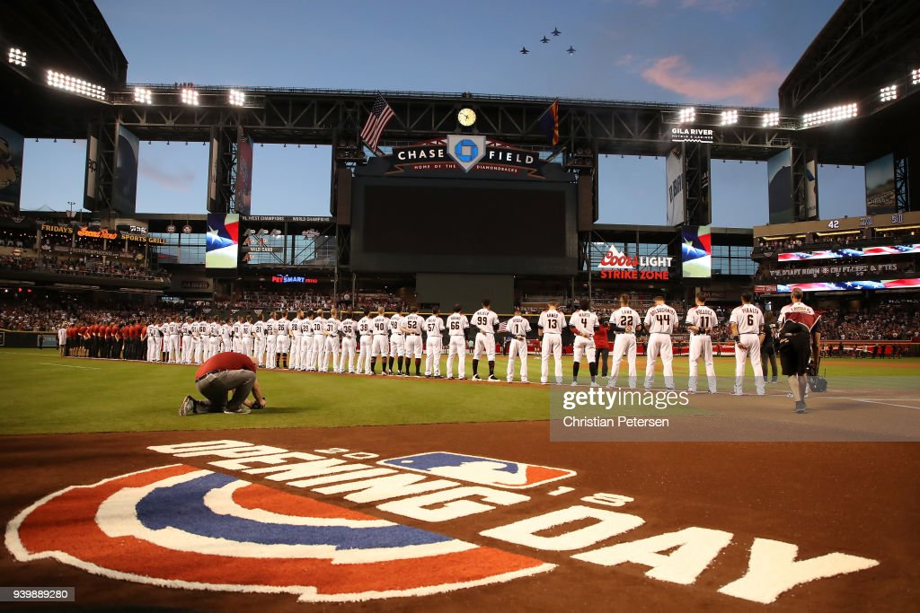 The Arizona Diamondbacks stand attended for the national anthem prior to the openning day MLB game against the Colorado Rockies at Chase Field on March 29, 2018 in Phoenix, Arizona.