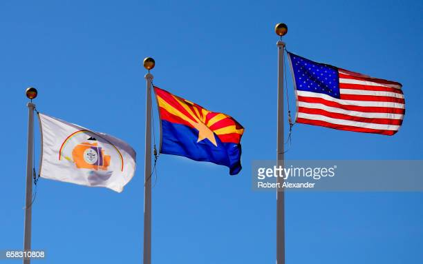 The Arizona state flag flies between the United States flag and the Navajo Nation flag at the Visitor Center at Canyon de Chelly National Monument...