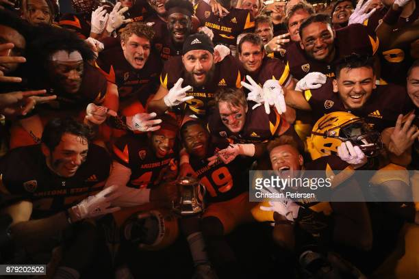 The Arizona State Sun Devils celebrate with the territorial cup after defeating the Arizona Wildcats in college football game at Sun Devil Stadium on...