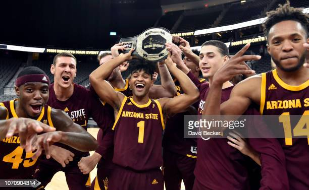 The Arizona State Sun Devils display the championship trophy after defeating the Utah State Aggies 8782 in the MGM Resorts Main Event basketball...