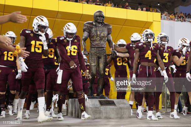 The Arizona State Sun Devils walk past a Pat Tillman statue before the NCAAF game against the Sacramento State Hornets at Sun Devil Stadium on...