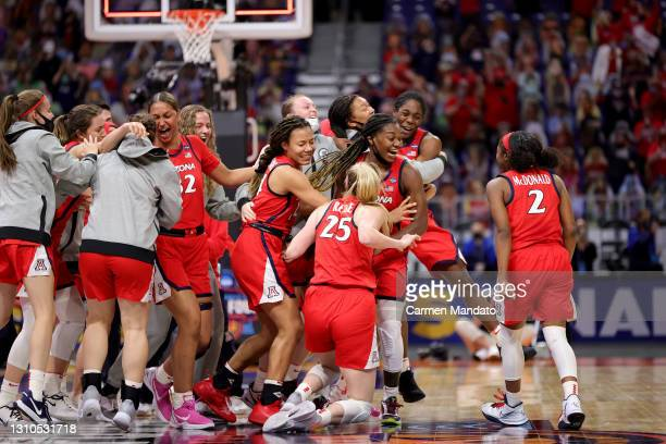 The Arizona Wildcats celebrate after defeating the UConn Huskies in the Final Four semifinal game of the 2021 NCAA Women's Basketball Tournament at...
